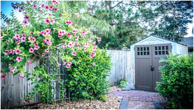 shed with brown doors at end of fence with flowers in front