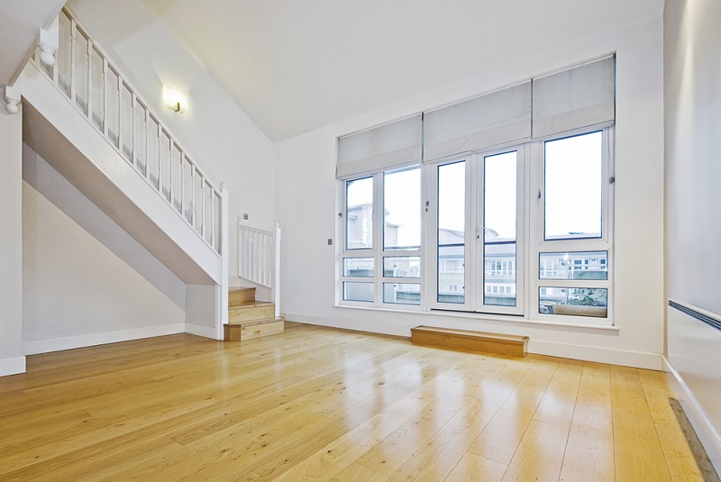 empty room with wood floor and roller blinds over the windows